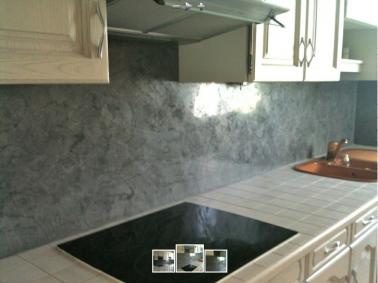 Pour repeindre entièrement cette cuisine, meubles bois et plan de travail en carrelage une même peinture ivoire. La crédence à l'allure moderne est repeinte avec de la chaux ferrée grise ultra brillante.