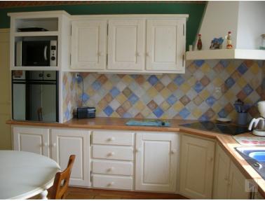 Pour repeindre cette cuisine en bois un peu vieillote une peinture blanc ivoire et pour une rénovation  complète de la cuisine la crédence en carrelage est recouvert d'une peinture carrelage de plusieurs couleurs.