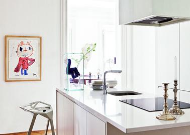 Dans une cuisine blanche une plaque de cuisson et un évier noir c'est sobre et chic. Le dessin croché au mur apporte la seule touche de couleur dans cette cuisine design