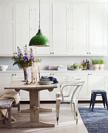 Dans une cuisine rustique les meubles repeints en blanc, la table de ferme et son banc en bois ajoutent une note chaleureuse de campagne chic