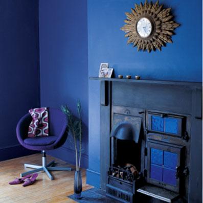 decoration salon tout en bleu : peinture murale, cheminée et fauteuil en contraste avec l'aspect chaleureux du parquet blond