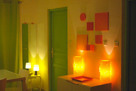 une salle a manger couleur peinture jaune pour les murs porte et encadrement couleur vert luminaire et tableaux decoratifs orange