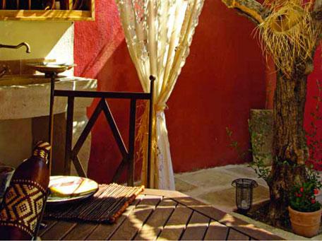 cuisine d'ete exterieur style provencal, peinture mur couleur ocre rouge, table en teck, chaise de jardin en fer,evier pierre