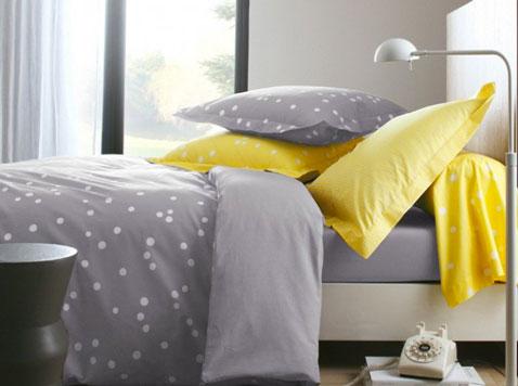 Décoration d'une chambre d'adulte en gris et jaune. La puissance du jaune des taies d'oreiller et du traversin illumine cette chambre construite autour du gris de la peinture murale et du linge de lit.