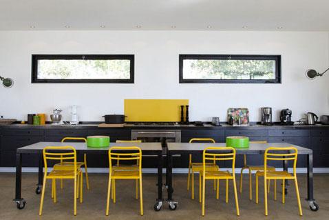 Dans une cuisine ouverte la couleur jaune de la crédence en verre et les chaises métalliques se conjuguent de façon très déco avec les meubles noir et la table industrielle