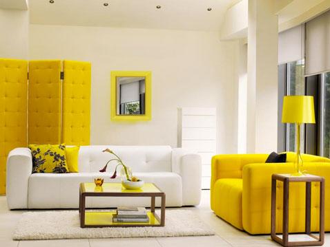 Déco d'un salon design autour d'un fauteuil en cuir jaune, une cloison paravent dans le même jaune et un rappel de couleur sur le cadre et le coussin qui illuminent le blanc pur dominant