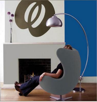 salon decoration design avec une composition de nuances de gris pour les peinture murale, cheminée contemporaine fauteuil coque revetement tissu gris lampadaire acier brossé