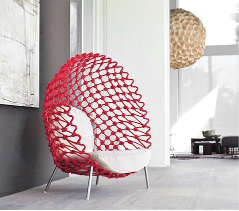 fauteuil coque très design la structure en tissu tordu de couleur rouge est montée sur de l'acier, coussin assise et dos tissu blanc