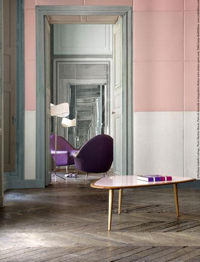 Murs d'un salon design revêtu de carreaux de cuir. carreaux de cuir blanc en soubassement, cuir rose sur hauteur, portes et plinthes peinture gris perle, deux fauteuils coque violet