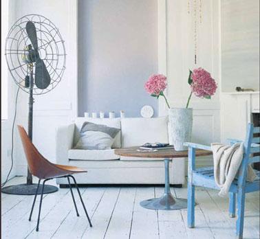Salon bleu et blanc avec un effet lumière pour les peintures en finition mat et satin. Pour conserver la pureté de l'ambiance, une chaine et une table basse en hêtre et un simple bouquet de fleurs rose pale