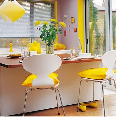 dans une cuisine blanche, quelques touches de jaune avec les coussins de chaises, la suspension quelques accessoires dynamisent facilement l'ambiance de la cuisine