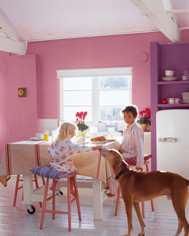 Une décoration de cuisine aux couleurs acidulées. Rose vif pour la peinture mural meuble étagères peint en violet, chaises peintes en rose soutenu