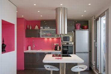 Cuisine design en rose et gris. Les meubles en gris soutenu contratent avec la couleur rose vif de la peinture murale. Frigidaire et hotte en inox