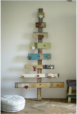 Calendrier de l'avent en forme de sapin de Noël réalisé avec des planches de récup et décoré de petits coeur et sujets rouges faits maison