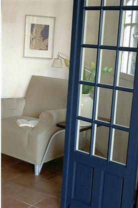 Une décoration de salon travaillée en contraste avec une peinture murale en gris blanc, un fauteuil dans un doux ton de gris mastic. Le bleu intense de la peinture de la porte crée un joli contraste
