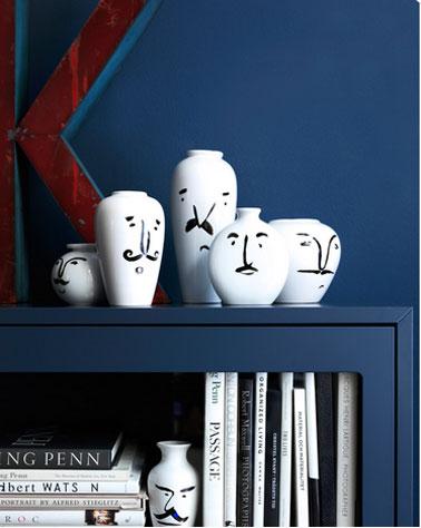 Pour agrandir le salon, la bibliothèque et les murs sont peints dans la couleur, Le bleu monaco. La série de vase blanc apporte un contraste fort.