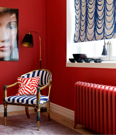 Un salon à la décoration ambiance boudoir contemporain. Peinture murale rouge vif, rideau bleu et blanc fauteuil style recouvert tissu rayé blanc et bleu