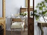 Dans un séjour zen, la déco de table de Noël se fait à l'unisson, nappe en coton et lin, bougie blanche et déco du centre de table avec une composition de feuillages légers