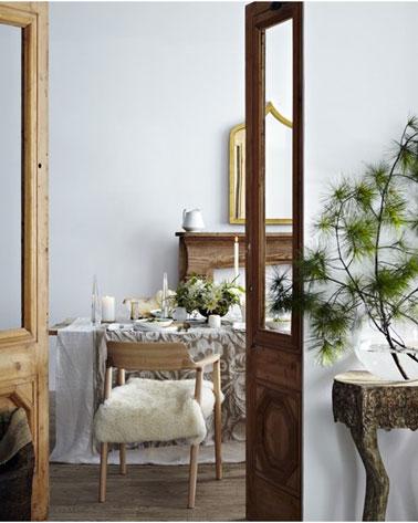 Sur la table de Noël d'une salle à manger à la déco zen, des nappes en lin et coton en superposition mixant nappe blanche et lin décorée de bougies blanches et de branchages pour la touche couleur