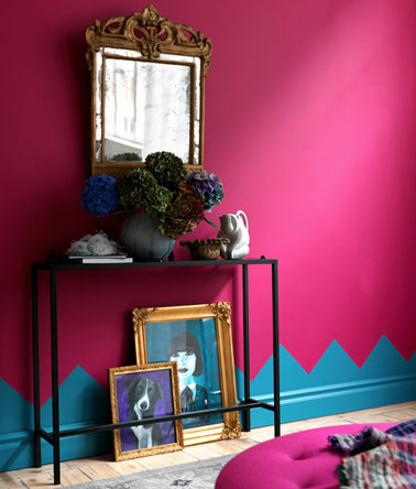 Décoration petit salon avec peinture couleur rose fushia, plinthes peintes avec motif sur mur en bleu vif. Console fer noir