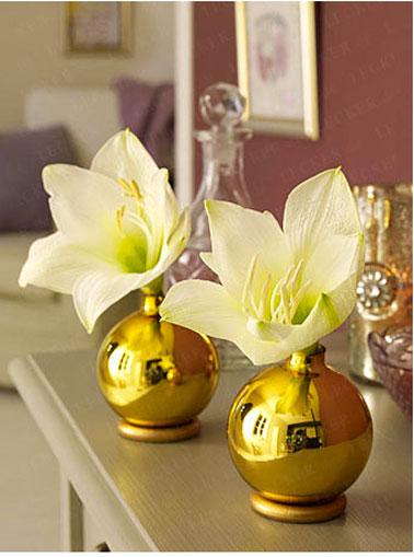 Pour la décoration de la table de Noël, un vase réalisé avec des boules dorées et des anneaux dorés à la bombe