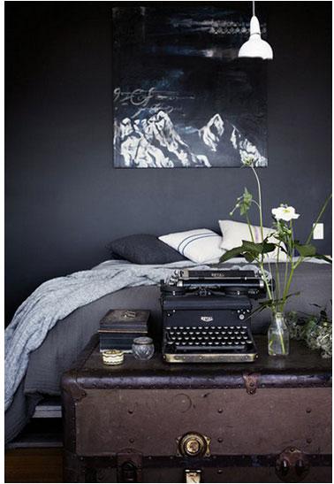 Chambre d'adultes déclinée dans des tons de noirs et gris. Aux murs, une peinture gris anthracite finition mat. Linge de lit et coussins gris et blanc.
