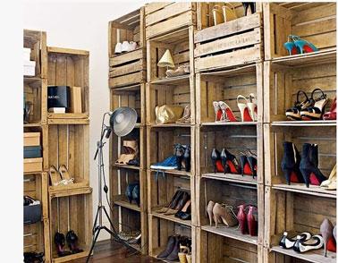Pratique pour ranger des tas de chaussures, un dressing composé à partir de caisses en bois empilées les unes sur les autres sur toute la hauteur des murs de la pièce.