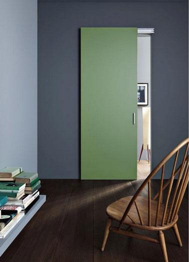 Porte de communication entre salon salle à manger peinte en vert jade en harmonie avec le gris perle et le gris anthracite des murs. Au sol, parquet wengé