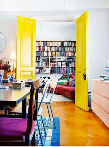 Entre salon et salle à manger, porte peinte en jaune vif, murs blanc, coussins chaises violet, canapé rouge
