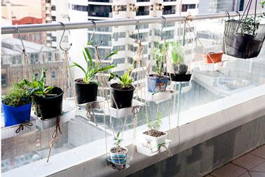 aménagement suspension pour fleurs et plantes aromatiques sur un balcon. Suspensions petites plantes fabriquées avec pots de culture et containers de récupération