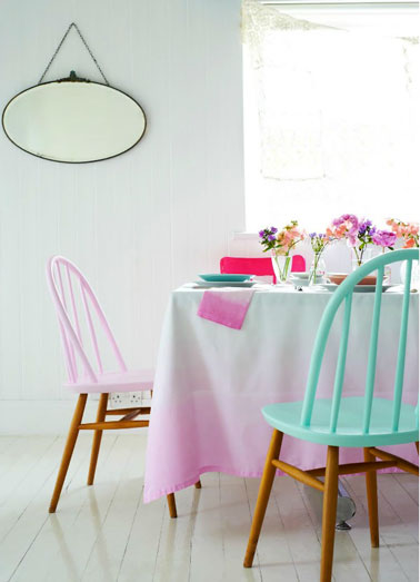 Ambiance printanière dans une salle à manger blanche apportée par les couleurs pastel utilisées pour repeindre l'assise et le dossier des chaises en bois et l'explosion des couleurs utilisées pour la décoration de la table.