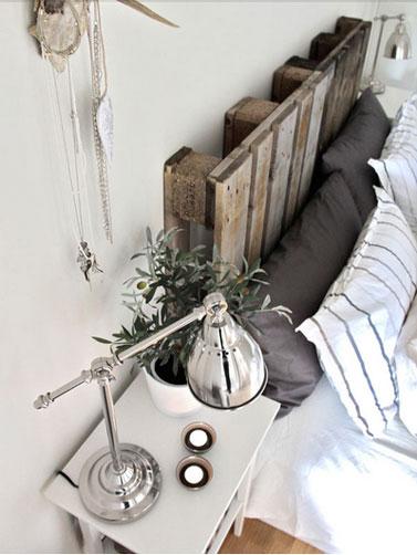 Dans une chambre d'adulte, la tête de lit fabriquée avec deux palettes de bois brute pour complèter l'ambiance couleurs naturelles de la chambre