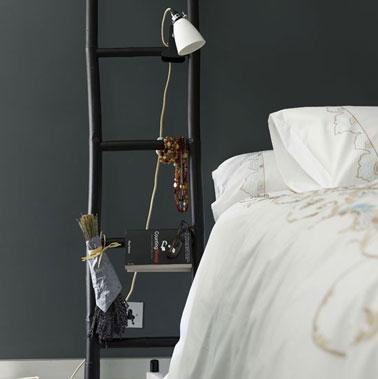 table de nuit dans chambre noir et blanc réalisée à partir d'une échelle en bois peinte en noir satin. Le spot de lumière est accroché sur une barre de l'échelle.