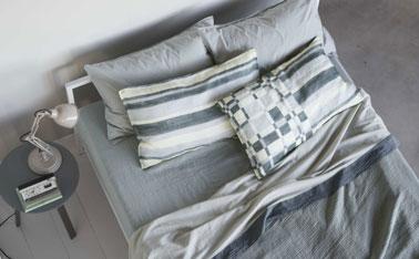 déco de chambre dans une belle harmonie de gris pastel et blanc. Le parquet, les murs sont peints dans le même gris tendre, le linge de lit reprend le thême du gris dans des tonalités légèrement plus soutenues. Les taies d'oreiller à rayures et carreaux apportent une touche de fantaisie dans cet univers monochrome