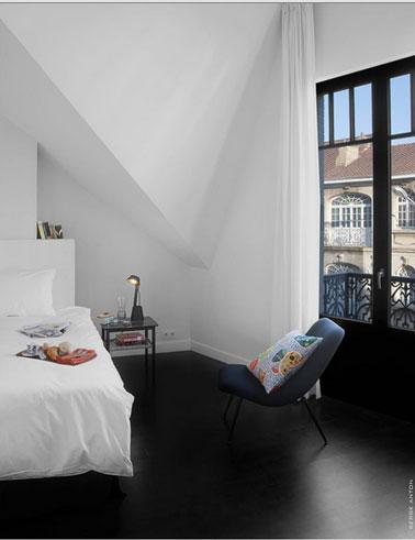Décoration chambre sous les toits en noir et blanc. Fauteuils bleu coussin à fleurs.
