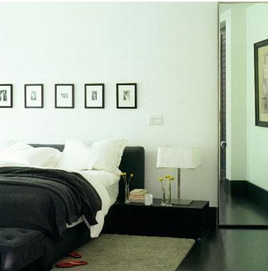 Déco chambre en noir et blanc. Peinture murs blanc pur. sol peint en noir brillant, table de nuit noir laqué linge de lit noir et blanc.