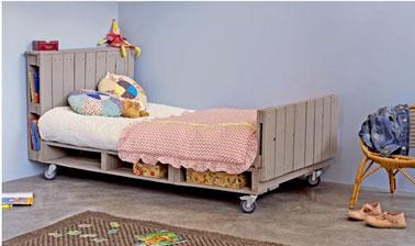 Un lit pour enfant où l'épaisseur des palettes du sommier est utilisée pour le rangement des jouets dans des paniers en osier et où la tête de lit palette sert elle à ranger les livres et bibelots.