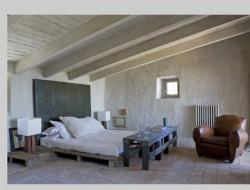 LIt fait avec palette en bois dans une chambre esprit loft. Cevets et pied de lit également en palette de bois.