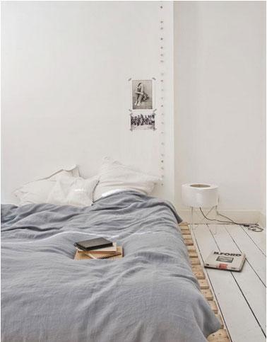 La déco d'une chambre ambiance zen avec un lit en palette dont le bois est laissé brut. Sur les murs peints en blanc pur une guirlande lumineuse borne l'espace de la tête de lit.