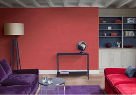 Décoration salon avec enduit décoratif effet terre naturelle couleur rouge rubis, canapé et tapis couleur prune