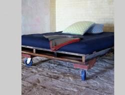 Décoration chambre design brut avec lit en palette bois montées sur roulettes.