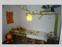 lit chambre petite fille réalisé avec des palettes bois. La petite barrière de protection est réalisée avec des tasseaux plats teintés en marron