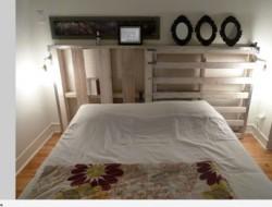Lit chambre adulte fait avec des palettes bois. La tête de lit également en palette permet des rangements et sert également d'étagère pour présenter des cadres photos