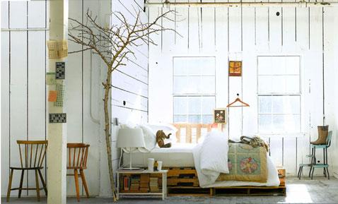 Déco chambre style scandinave avec lit réalisé avec des palettes de bois laissées brutes.Linge de lit blanc pur, chaises vintage complètent la décoration