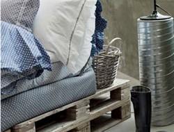Le linge de lit et le confort des multiples oreillers de ce lit réalisé avec des palettes bois apportent une note douillette dans cette chambre où les matériaux bruts, bois, béton et zinc dominent