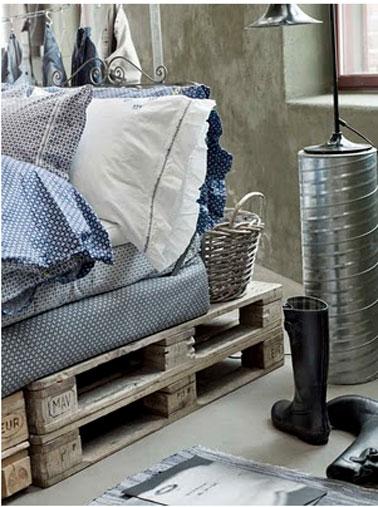 Ambiance cosy et style récup s'associe autour du lit en palette recouvert d'un linge de lit bleu et blanc