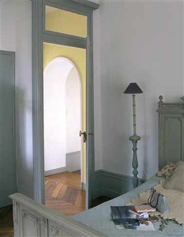 Un doux ton de peinture verte pour repeindre murs et meubles anciens dans une chambre,  associé à un gris clair sur les murs. Sur la tête de lit en bois la même peinture vert mousse que pour l'armoire de Tollens.