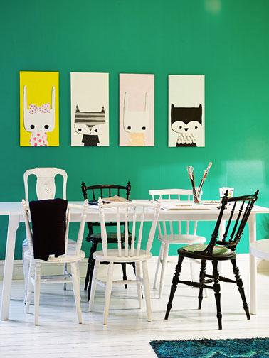 Salle à manger avec chaises en bois dépareillées. Deux chaises peintes en noir brillant contrastent avec le blanc pur de la table et des autres chaises. L'ensemble est mis en valeur avec la couleur vert émeraude de la peinture murale
