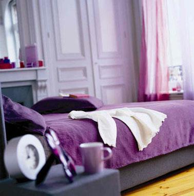 Deco chambre adulte. Peinture chambre couleur violet lila associée à une parure de lit et des coussins violet intense