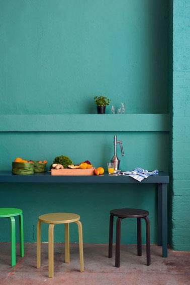 Pour donner du tempérament à la déco de sa cuisine avec la peinture on mixte les couleurs intenses. Murs vert intense, table bleu turquoise, tabourets vert et noir avec la peinture Maître en Couleur